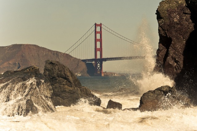 View of Golden Gate Bridge from Baker Beach, with crashing wave.